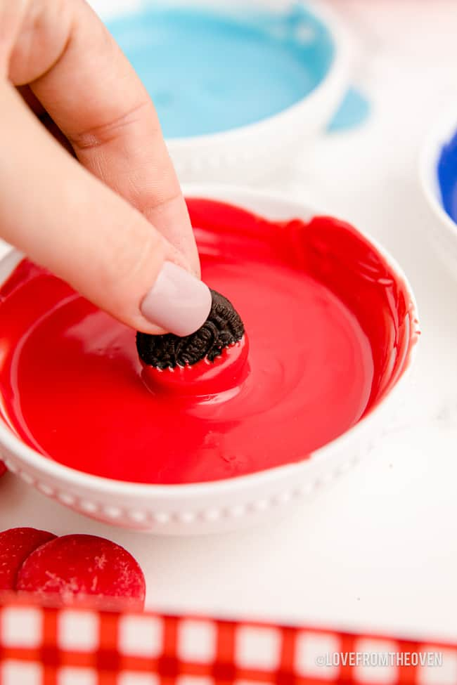 an oreo being dipped in red candy coating