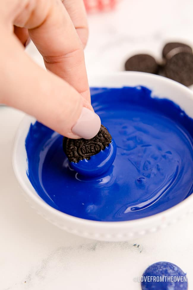 an oreo being dipped in chocolate