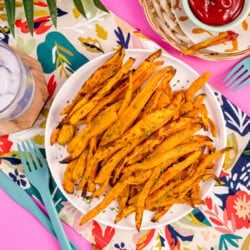A plate of air fryer sweet potato fries on a pink background.