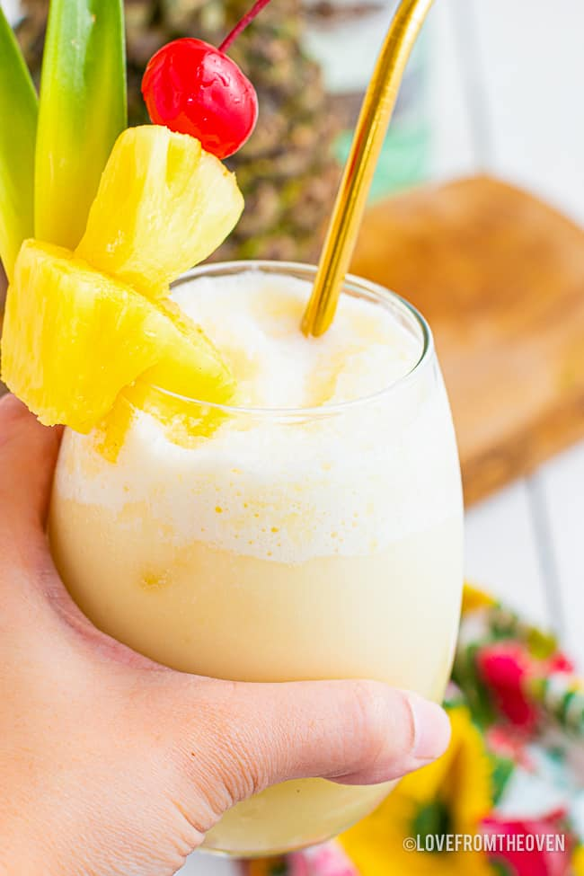 A hand holding a glass of pina colada.