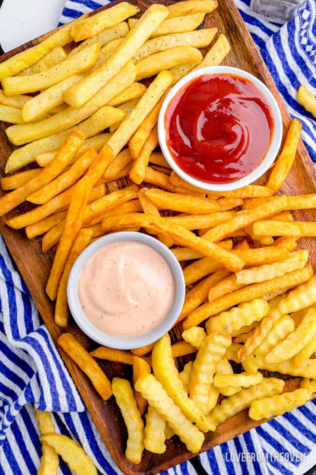 a variety of french fries on a platter with dipping sauces.
