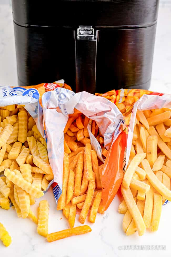 Bags of frozen french fries in front of an air fryer.