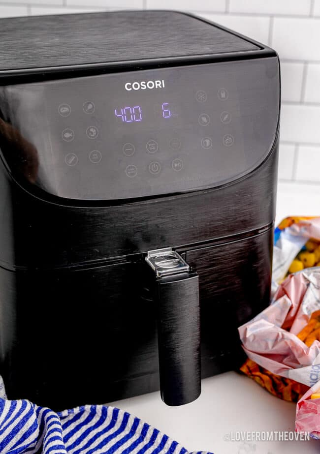 A black air fryer on a countertop.