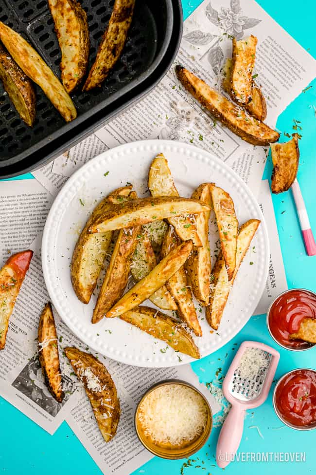 Potato wedges on a plate and in an air fryer.
