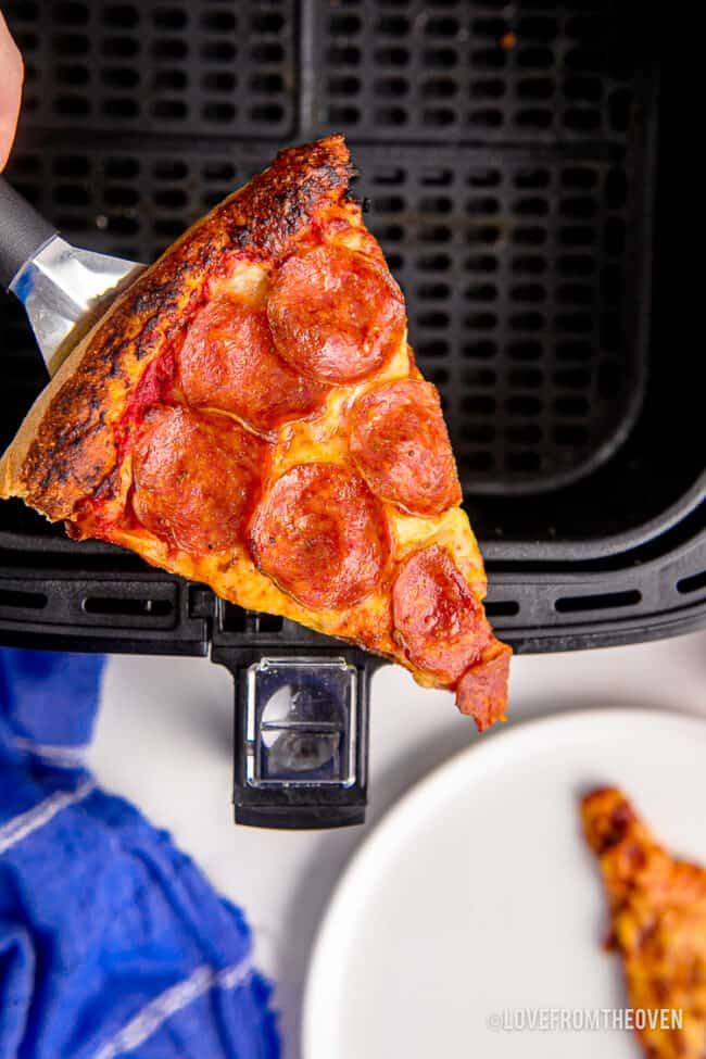 A slice of pizza in an air fryer.
