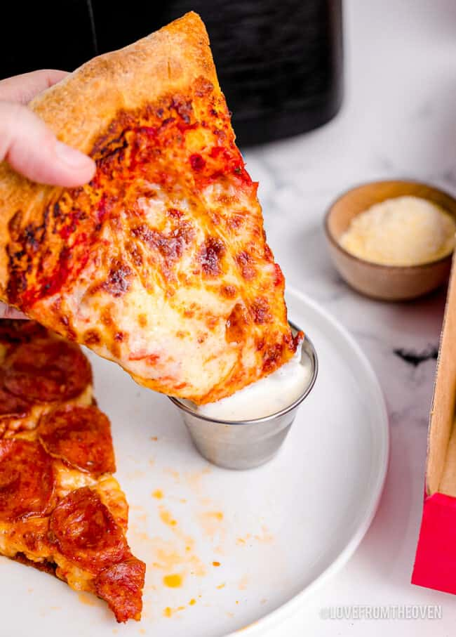 A slice of pizza being dipped in ranch dressling.