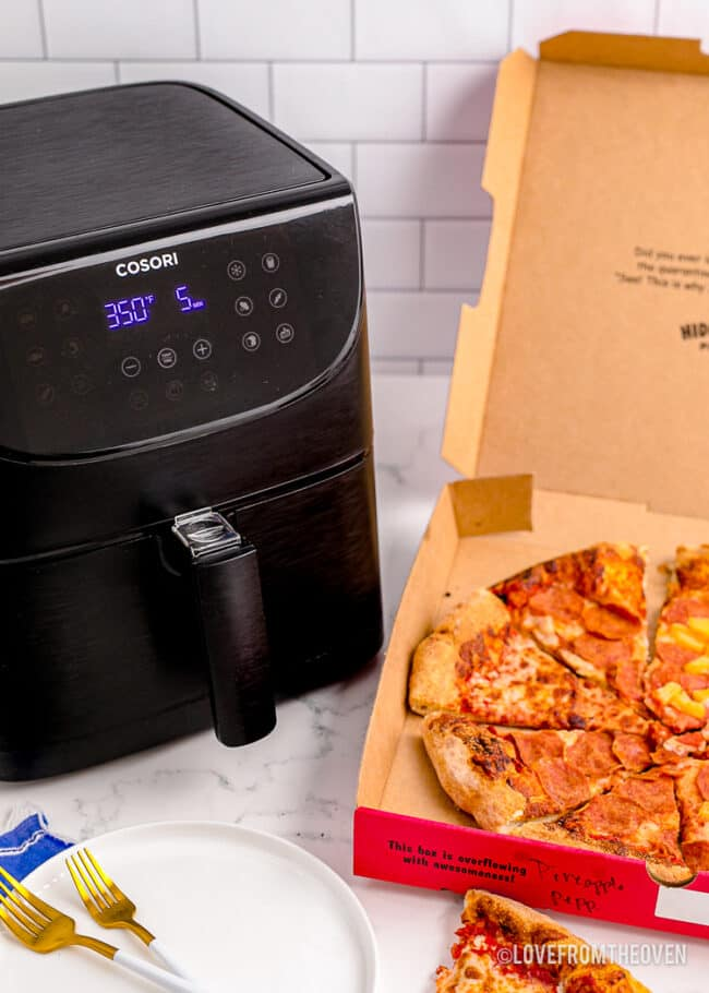 An air fryer and a box of pizza to be reheated.
