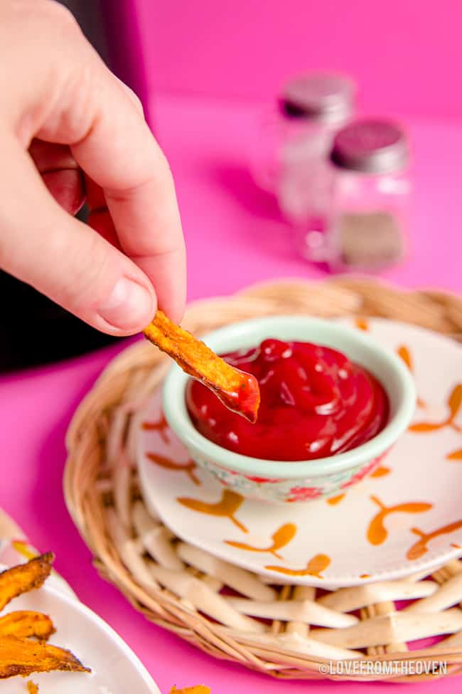 A sweet potato fry being dipped in ketchup.