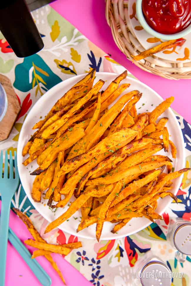A plate of sweet potato fries on a pink background.