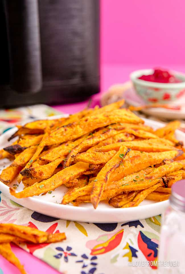 Sweet potato fries in front of an air fryer.