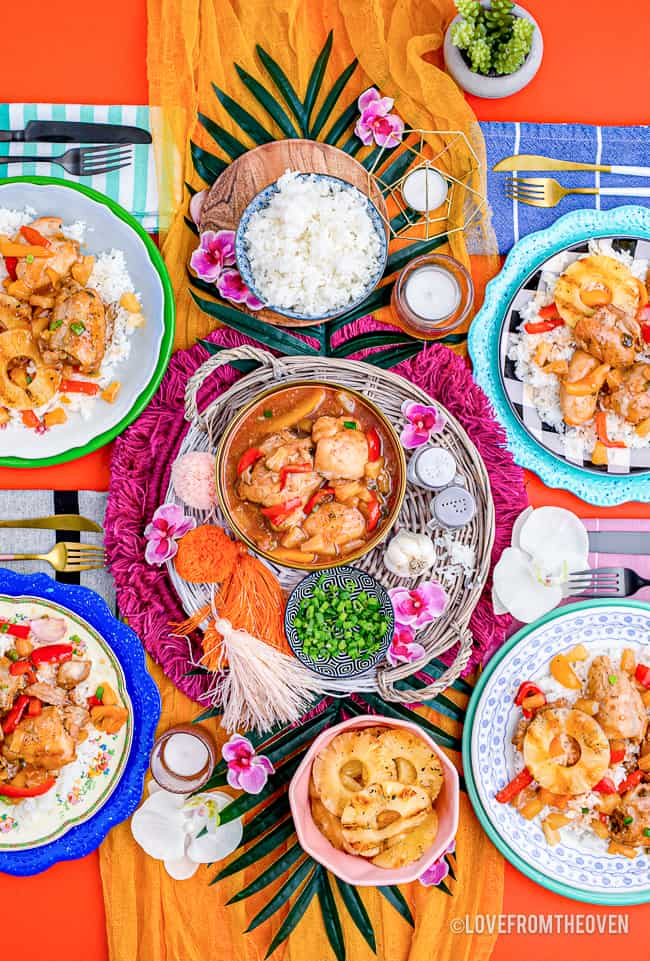 A colorful dinner table with crockpot Hawaiian chicken being served.