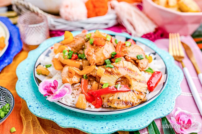 A plate of Hawaiian chicken with a colorful background.