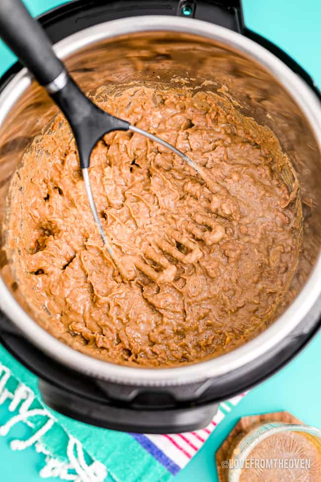 Refried beans in an instant pot being mashed.