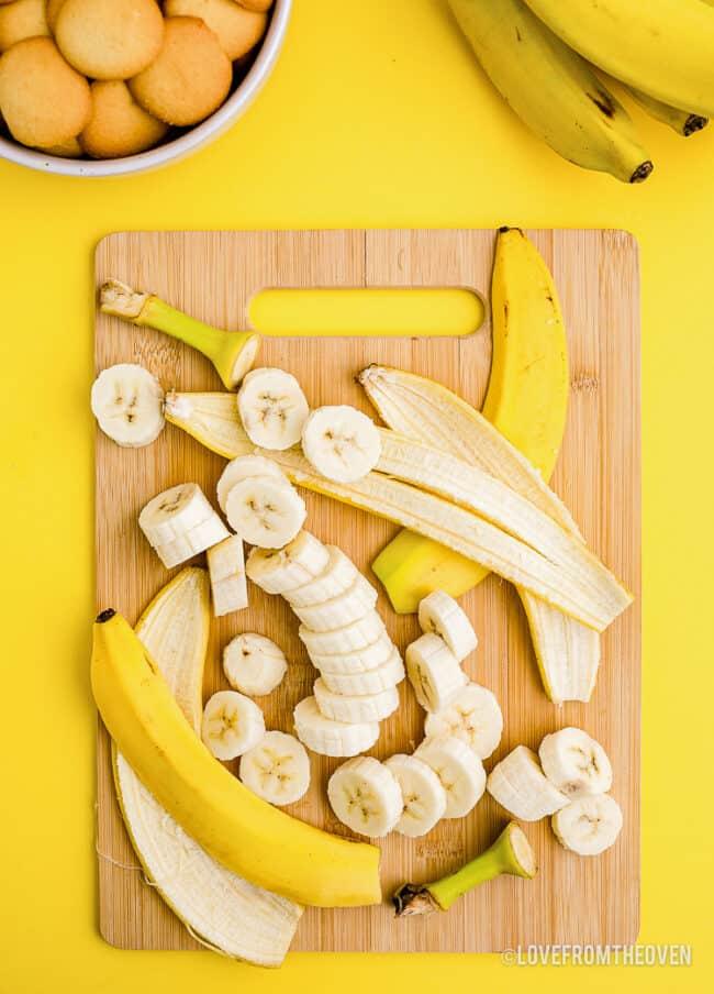 A banana cut up on a cutting board.