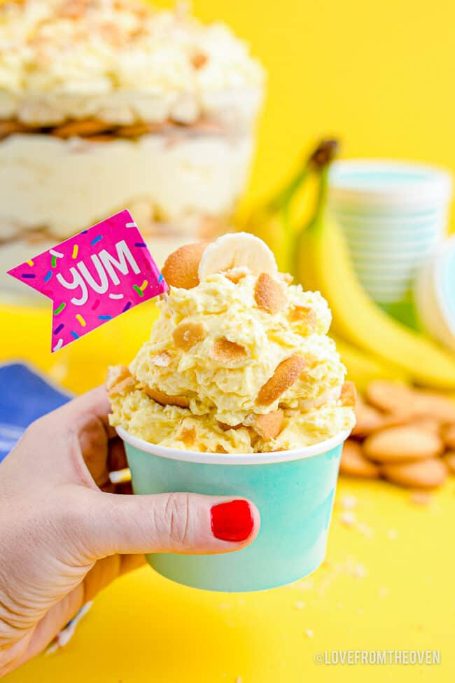 A cup of banana pudding with nilla wafers in an aqua cup.