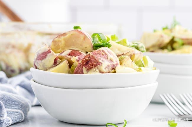 Potato salad in a white bowl.