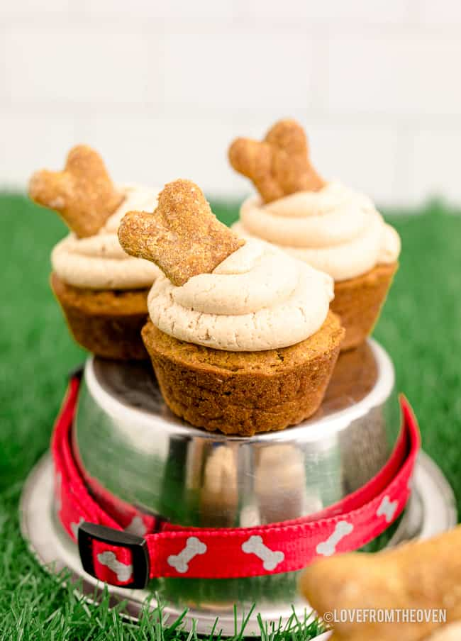 Dog cupcakes sitting on a metal dog dish.