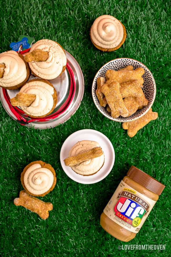 Dog cupcakes and dog bones on grass.