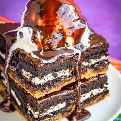 Cookie Dough Brownies with ice cream and chocolate sauce on a plate.