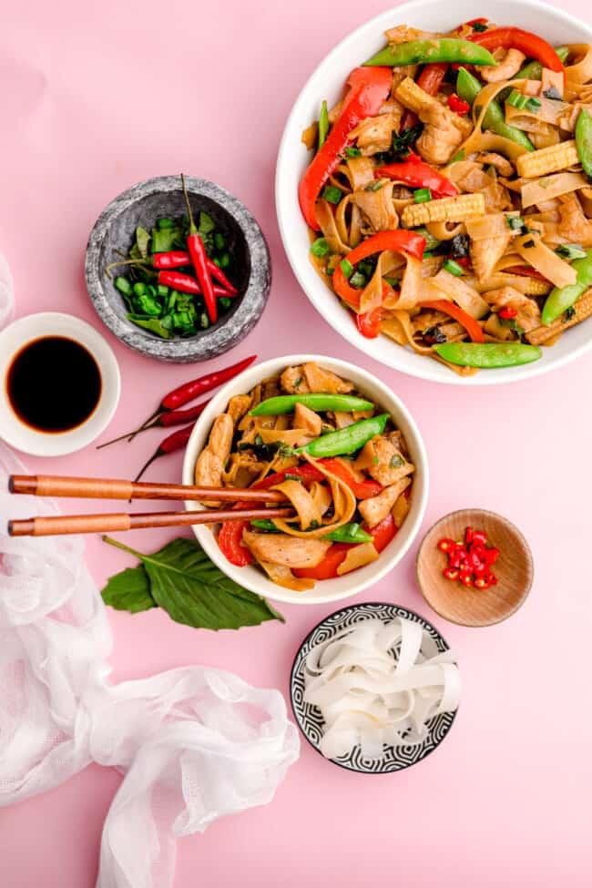 Photos of Thai drunken noodles on a pink background.