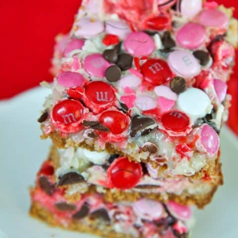 Magic cookie bars with pink and red mms on top.