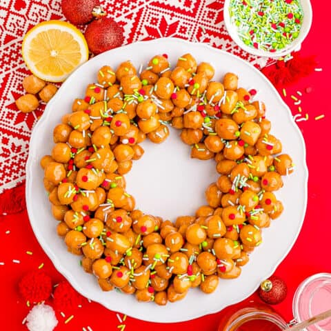 Struffoli on a white plate with a red background.