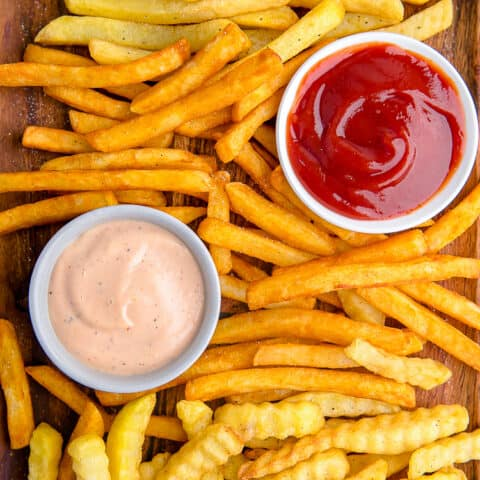French fries on a baking sheet with dipping sauces.