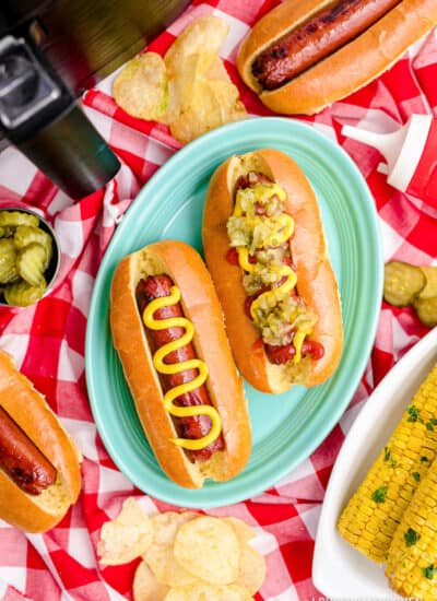 Two hot dogs in front of an air fryer.
