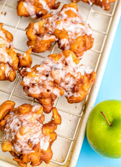 Apple fritters on a baking sheet.