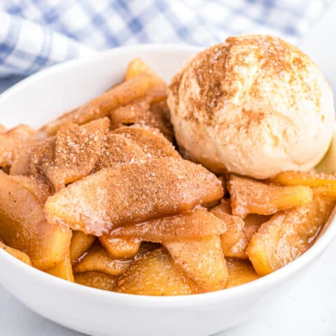 A bowl of baked cinnamon apples with a scoop of ice cream.