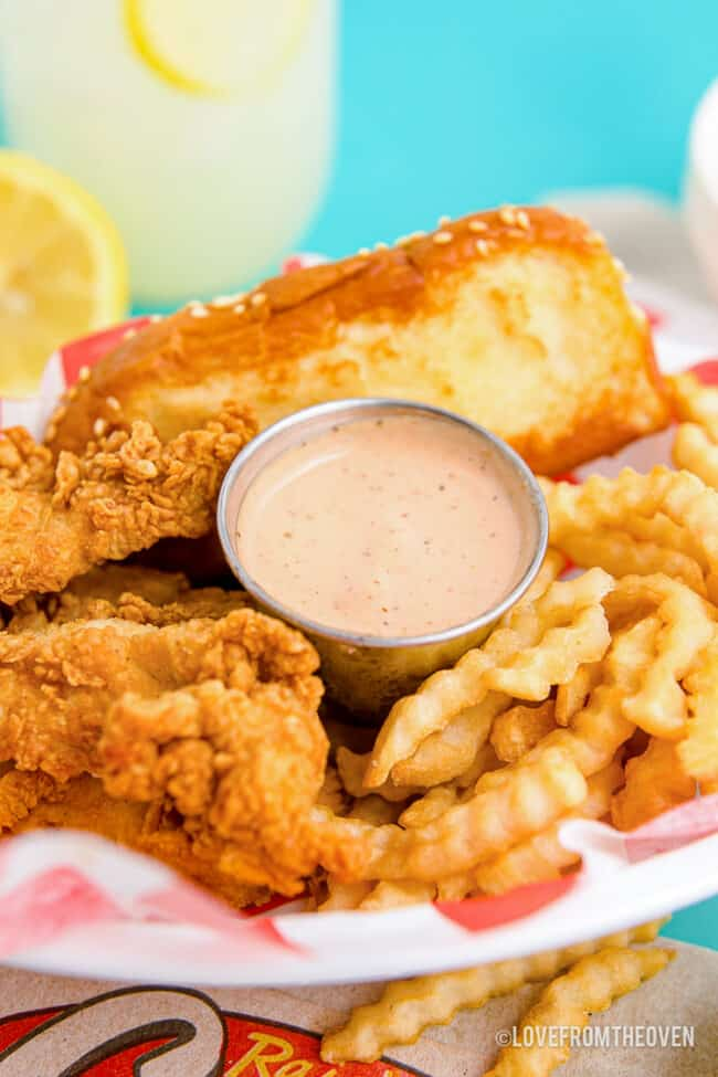 Photo of canes sauce with chicken and fries.