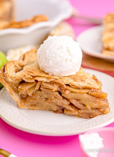 A slice of apple pie with vanilla ice cream on top.