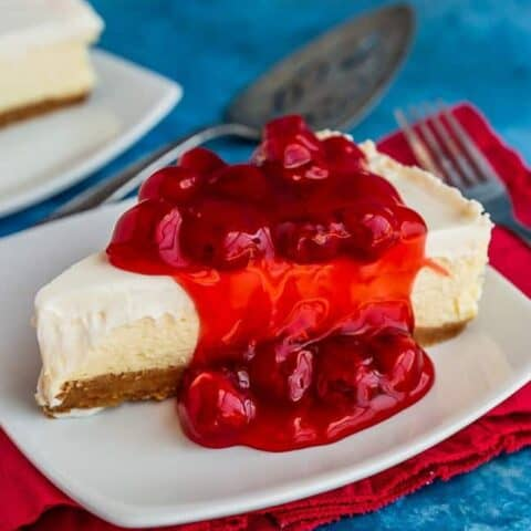 A photo of a slice of cheesecake with cherries on top.