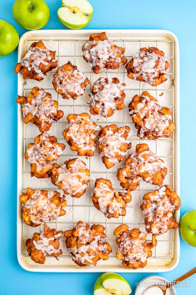 A baking tray full of homemade apple fritters.