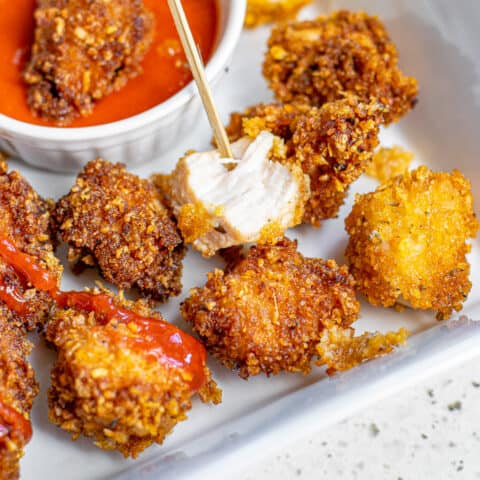 Popcorn chicken next to a dipping sauce.