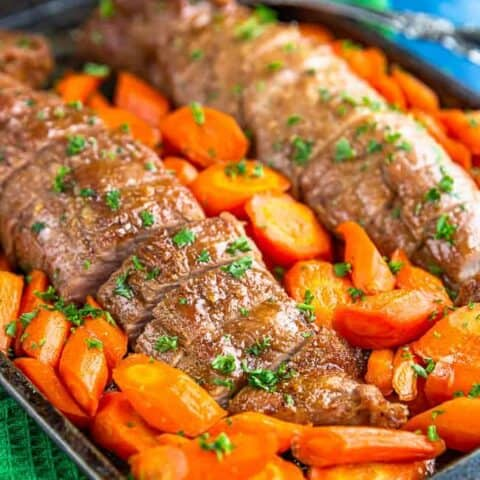 Pork tenderloin with carrots on a baking sheet.