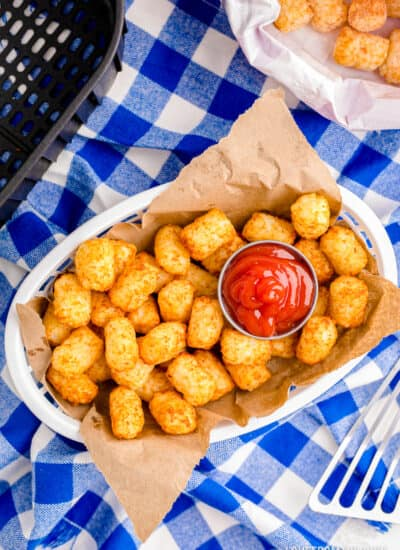A basket of air fryer tater tots on a blue and white background.