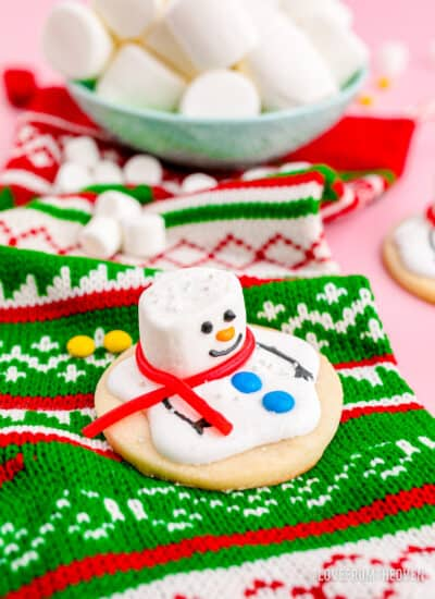 A melted snowman cookie on a christmas stocking.